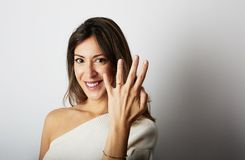 Happy european girl with long dark hair in stylish clothes smiling and holding hand on hip while showing trendy wedding. Ring over empty white wall background royalty free stock photos