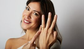 Happy european girl with long dark hair in stylish clothes smiling and holding hand on hip while showing trendy wedding. Ring over empty white wall background stock images