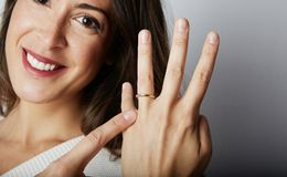 Happy european girl with long dark hair in stylish clothes smiling and holding hand while pointing finger trendy wedding. Ring over empty white wall background stock photography