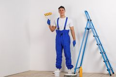 Happy construction worker, in blue uniform, holds a paintbrush and a roller and smiles. Happy European male construction worker, dressed in blue uniform, holds Stock Image