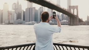 Happy European male tourist comes up to river embankment near Brooklyn Bridge, New York, takes photo and smiles 4K. Happy European male tourist comes up to stock video