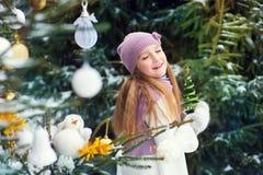 Happy european toddler girl outdoors near xmas tree, decorated w Royalty Free Stock Image