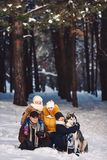 Happy european young family with big dog posing against winter pine forest royalty free stock image