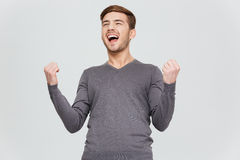 Happy excite young man screaming and celebrating his succcess. Happy excite young man in grey pullover screaming and celebrating his succcess over white Stock Image