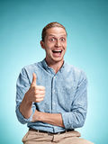 Happy excite young man smiling over blue background. Happy excite young man in blue shirt smiling and celebrating his succcess over blue studio background Royalty Free Stock Photos