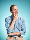 Happy excite young man smiling over blue background. Happy excite young man in blue shirt smiling and celebrating his succcess over blue studio background Royalty Free Stock Image