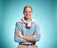Happy excite young man smiling over blue background. Happy excite young man in blue shirt smiling and celebrating his succcess over blue studio background Stock Image