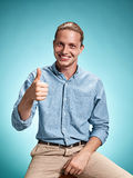 Happy excite young man smiling over blue background. Happy excite young man in blue shirt smiling and celebrating his succcess over blue studio background Stock Photos