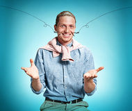 Happy excite young man smiling over blue background. Happy excite young man in blue shirt smiling and celebrating his succcess over blue studio background Royalty Free Stock Photo