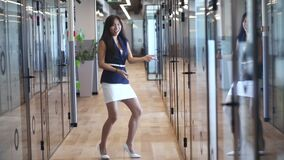 Happy excited asian business woman dancing in hallway, slow motion