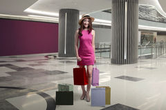 Happy excited asian woman with hat holding shopping bags Royalty Free Stock Photography