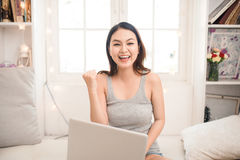 Happy excited asian young woman working on a laptop at home. Stock Photos
