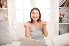 Happy excited asian young woman working on a laptop at home. Royalty Free Stock Photography