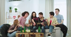 In a happy and excited big company of friends multi ethnic in a spacious living room on the sofa a guy playing on a stock footage