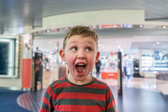 Happy and excited boy in front of a store eager to go in shopping. Making funny face. Happy and excited boy in front of a store eager to go in shopping. Making Stock Photos