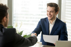Happy excited business partners handshaking after signing mutual. Happy business partners handshaking after signing mutually beneficial contract, businessmen Royalty Free Stock Image