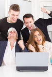 Happy excited business people winning online looking at laptop c Royalty Free Stock Images