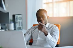 Happy excited businessman celebrate his success. Winner, black man in office reading on laptop.  Stock Photography