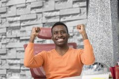 Happy excited businessman celebrate his success. Winner, black man in office reading on laptop, copy space.  Stock Photos
