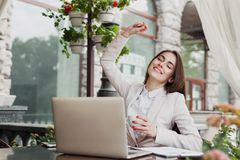 Happy excited businesswoman celebrate. Victory with arm raised in the air. Winner, successful caucasian woman outdoors sitting at summer terrace cafe, lifestyle Stock Photo