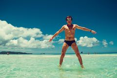 Happy excited cheerful funny man in swimming goggles enjoying summer beach vacation. Time to travel. Stress free concept. Shirtles. S athletic male body. Exotic Royalty Free Stock Image