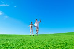 Happy excited couple jumping together. Happy couple jumping together holding hands on a green field Royalty Free Stock Image