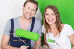 Happy excited couple painting their new home. Happy excited attractive young couple painting their new home bright green posing together smiling at the camera Stock Photo