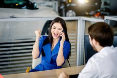 Woman buying a new car talking on smartphone. Happy excited customer female screaming with delight getting the aproval on bank loan buying a new car stock image