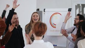 Happy excited diverse business people join hands celebrating team success with young male boss at healthy workplace. Cheerful colleagues shout, smile and stock video