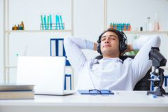 The happy excited doctor listening to music during lunch break in hospital. Happy excited doctor listening to music during lunch break in hospital Stock Photo