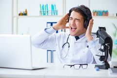 The happy excited doctor listening to music during lunch break in hospital. Happy excited doctor listening to music during lunch break in hospital Royalty Free Stock Photos