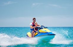 Happy, excited family, father and son having fun on jet ski at summer vacation. Happy, excited family, father and son having fun together on jet ski at summer stock photos