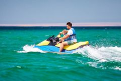 Happy, excited family, father and son having fun on jet ski at summer vacation. Happy, excited family, father and son having fun together on jet ski at summer stock photography