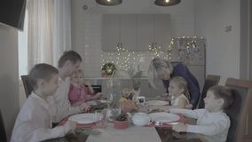 Happy excited family of six celebrating lovely Christmas dinner in festive atmosphere cozy kitchen. Happy lovely excited family of six celebrating Christmas stock video footage