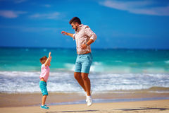 Happy excited father and son jumping on summer beach, enjoy life. Together stock photography