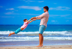 Happy excited father and son playing on summer beach, enjoy life. Together Royalty Free Stock Photography