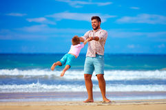 Happy excited father and son playing on summer beach, enjoy life. Together Royalty Free Stock Image