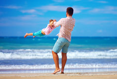 Happy excited father and son playing on summer beach, enjoy life. Together stock photo