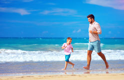 Happy excited father and son running on summer beach, enjoy life. Happy excited father and son playing on summer beach, enjoy life together stock photos