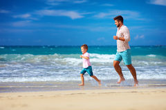 Happy excited father and son running on summer beach, enjoy life Royalty Free Stock Photo