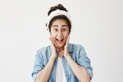 Happy excited female has dark hair, wearing do-rag and denim shirt, glad to see something unexpected, keeps hands on. Cheeks, smiles broadly, isolated against Royalty Free Stock Photo