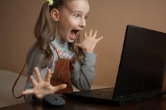 Free Happy Excited Girl Is Studying At Home With Her Teacher Using Video Chat Online On Her Black Laptop Because Of The Self Stock Photos - 179215263