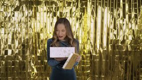 Happy excited girl opens a box with a gift. Golden light shines on her face from the box. Woman on a gold background. 4K stock video