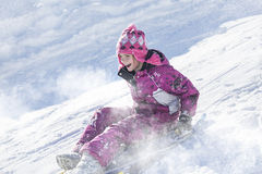 Happy and excited girl Sledding downhill on a snowy day Stock Photography