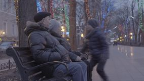 Happy excited grandchild boy running over to grandparents sitting on bench in christmas festive atmosphere evening park stock video footage