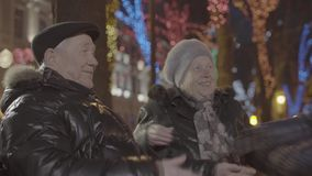 Happy excited grandson boy running over to old granparents hugging in cozy festive atmosphere christmas evening park stock video footage