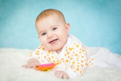 Free Happy Excited Infant Baby Girl Lying On The Bed With White Fur On Bright Blue Background Stock Photo - 173736750