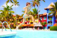 Happy excited kid jumping in pool on summer vacation Stock Images