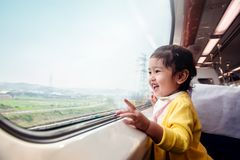Happy and Excited Kids Traveling by Train. A Two Years old Girl. Pointing her hand to Outside View, Sitting Near Wide Glass Window and Smiling royalty free stock image