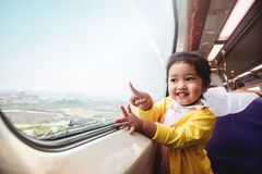 Happy and Excited Kids Traveling by Train. A Two Years old Girl. Pointing her hand to Outside View, Sitting Near Wide Glass Window and Smiling stock images